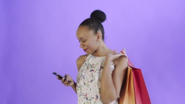 Portré afro-amerikai nő bevásárló táskák beszél okostelefonnal lila háttér stúdió. Fehér ruha virágokkal