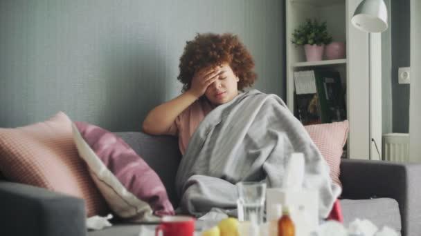 Bedeckt mit grau karierten jungen afrikanisch-amerikanischen Mädchen, die zu Hause eiskalt sind, krankes krankes Mädchen mit Fieber-Grippe-Temperatursymptomen