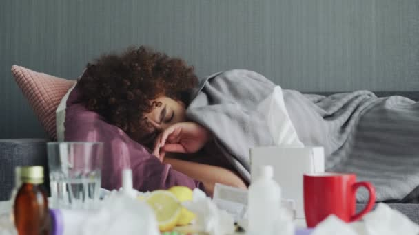 Kranke junge Afrikanerin schläft bei Krankheit entspannt auf Couch in Wohnung unter warmem Plaid.