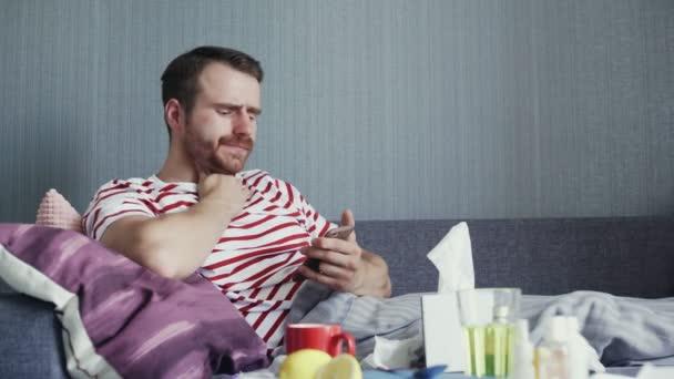 Kranker junger Mann benutzt Handy und pustet Nase mit Taschentuch