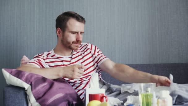 Ein erwachsener kranker Mann liegt auf dem Sofa und nimmt verschriebene Medikamente ein.