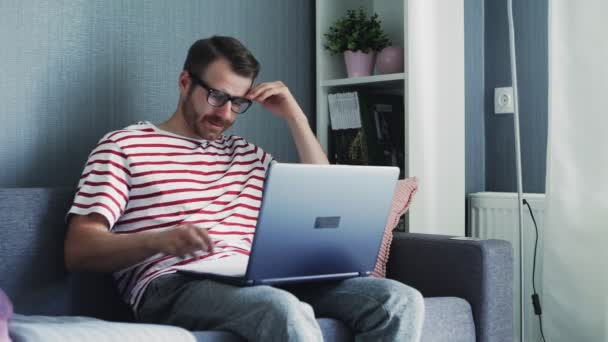 Tired Young Man with glasses works on a Laptop Holding it on His Lap and Sitting on a Sofa at Home.