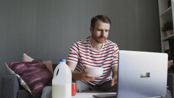 Bearded man eating cornflakes and using a laptop