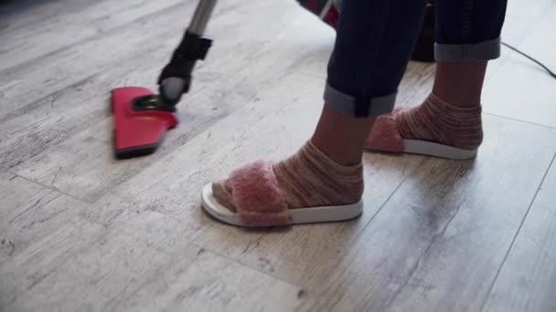 Mladá žena pomocí vysavače na podlahu