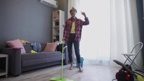 Happy young woman cute housewife is washing floor with mop and dancing at home