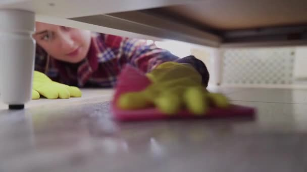 Close up of woman cleans the floor under bed with special detergent.