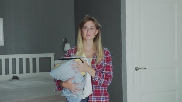 Junge Hausfrau hält saubere Kleidung und schaut in die Kamera