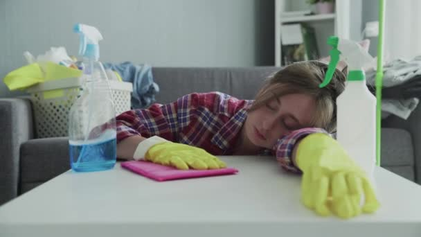 Müde Frau entfernt mit rosa Schwamm Staub vom Tisch