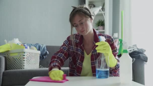 Tired woman using a pink sponge to trying hard removing dust from the table