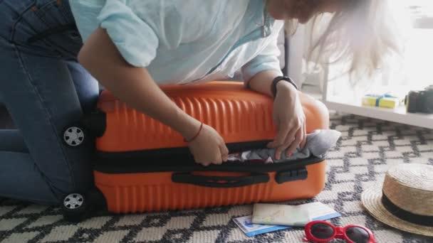 Mladá dívka stojí na Elbowsonovi na přeplněném oranžovém kufříku a snaží se ho zavřít.