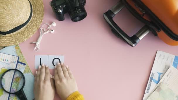 Horní pohled ruce ležící na růžovém stole slovo LONDÝN