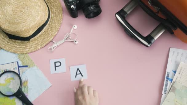 Horní pohled ruce ležící na růžovém stole slovo PAŘÍŽ