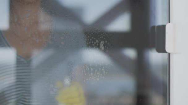 Mladá žena ve žlutých rukavicích mytí okna s modrým hadrem a čisticím prostředkem.