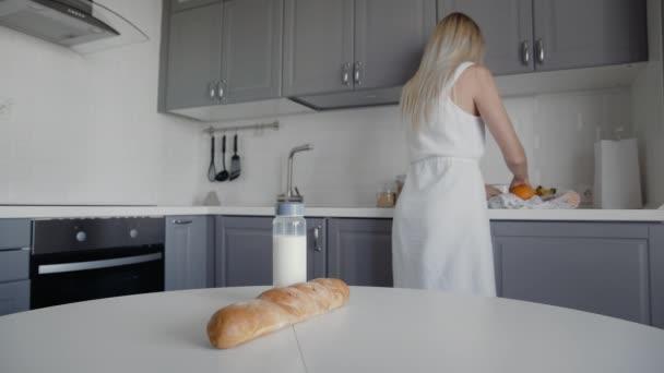 Blonďatá žena přesouvá chléb, ovesnou kaši, mléko, zeleninu ze stolu na polici. Nulový plýtvání domů a eko taška. Eco Shopping.