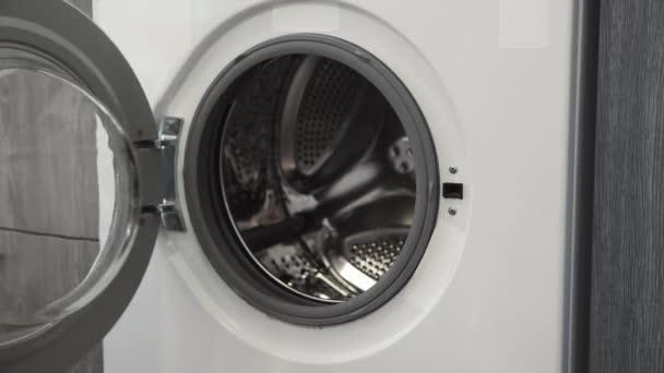 A női kéz fehér ruhát tett a mosógépbe. Mosógép betöltése. Ruhákat a mosógépbe. Ruha mosógép betöltése. Mosás előkészítése