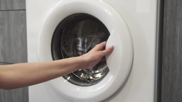 Weibliche Hand legt gefärbte Kleider in die Waschmaschine. Beladene Waschmaschine. Laden Sie Kleidung in die Waschmaschine. Laden Sie Wäschewaschmaschine. Waschen der Wäsche vorbereiten