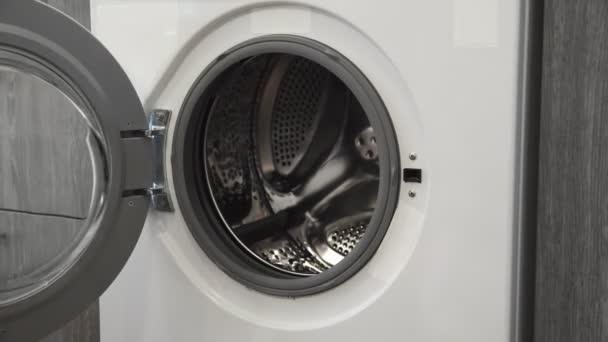 Weibliche Hand mit Ehering legt gefärbte Kleider in die Waschmaschine. Beladene Waschmaschine. Laden Sie Kleidung in die Waschmaschine. Laden Sie Wäschewaschmaschine. Waschen der Wäsche vorbereiten
