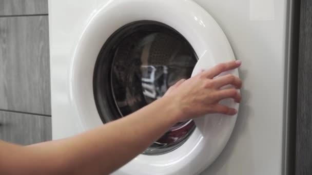Weibliche Hand nimmt gefärbte Kleider aus der Waschmaschine. Beladene Waschmaschine. Laden Sie Kleidung in die Waschmaschine. Laden Sie Wäschewaschmaschine. Waschen der Wäsche vorbereiten