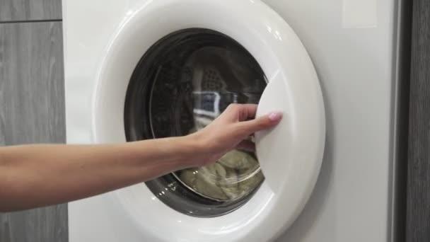 A női kéz kivesz két fehér SWEATert a mosógépből. Mosógép betöltése. Ruhákat a mosógépbe. Ruha mosógép betöltése. Mosás előkészítése