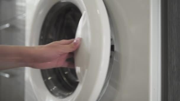Weibliche Hand mit Ehering legt weiße Kleider in die Waschmaschine. Beladene Waschmaschine. Laden Sie Kleidung in die Waschmaschine. Laden Sie Wäschewaschmaschine. Waschen der Wäsche vorbereiten