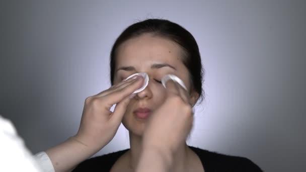 Studio portrét mladé, krásné a přírodní ženy nanášení krém na péči o pleť před make-up