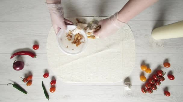 Top view of chef hands in white gloves puts chicken and french fries on doner kebab shawarma in pita or lavash. Cooking shawarma with chicken, french fries, cheese and vegetable