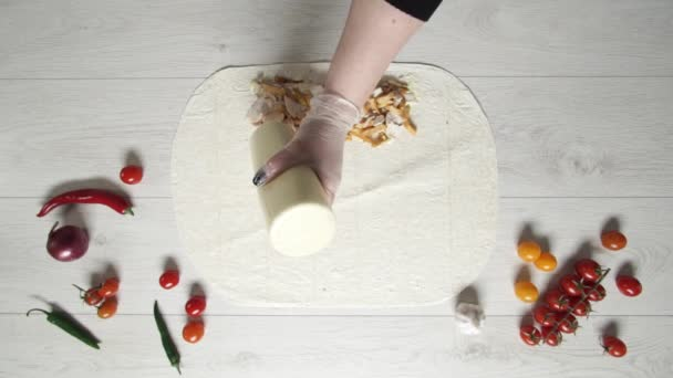 Top view of chef hands in white gloves puts souse on doner kebab shawarma in pita or lavash. Cooking shawarma with chicken, french fries, cheese and vegetable