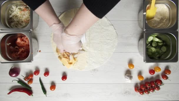 Chef hands in white gloves puts chicken and french fries on doner kebab shawarma in pita or lavash. Cooking shawarma with chicken, french fries, cheese and vegetable
