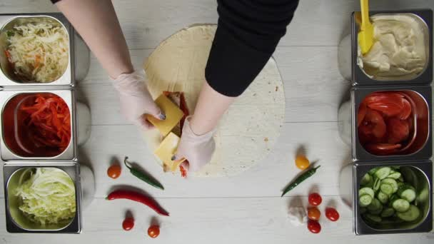 Top view of chef hands in white gloves puts cabbage on doner kebab shawarma in pita or lavash. Shawarma with chicken cutlet, pappers, cheese and vegetable