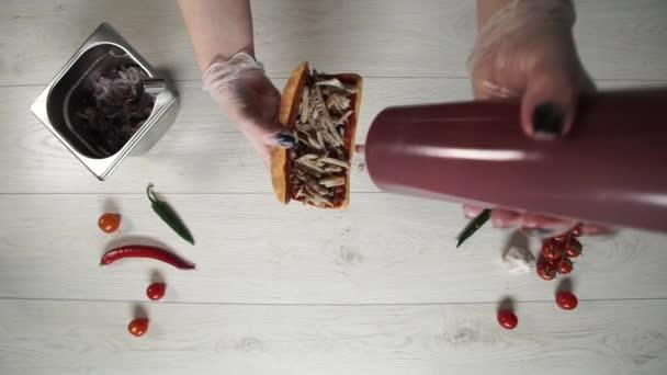 Von oben betrachtet kocht ein professioneller Koch im Fast-Food-Restaurant ein leckeres Sandwich. Köchin in Handschuhen steckt BBQ-Sauce in Sandwich