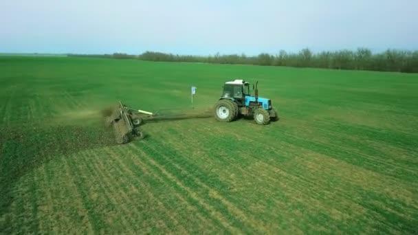 Farmář v traktoru se sazečem připravuje půdu k setí obilí na orané půdě. Zasazování semen do prachu. Jarní zemědělské práce. Aerial top view, drone fly forward follow tractor