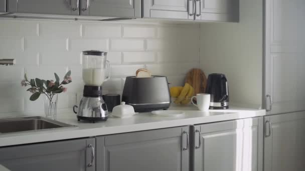 Empty kitchen with toaster, blender with cocktail, Electric kettle and glass bowl with lemon and banana