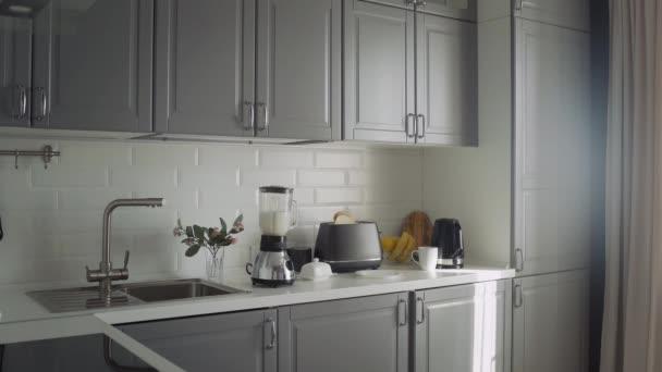 Prázdná kuchyň s toustovačem, mixér s koktejlem, rychlovarná konvice a skleněná mísa s citronem a banánem