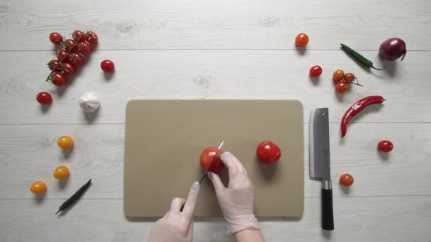 Chef cuts tomatoes on plastic board top view