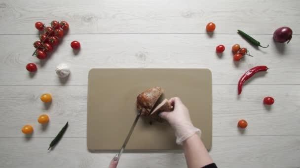 Chef cuts roast pork on plastic board top view