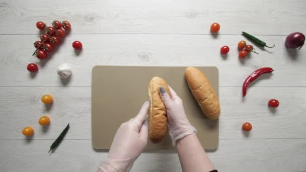 Top view of chif cuts white hot dog bread along. Cooking hot dog