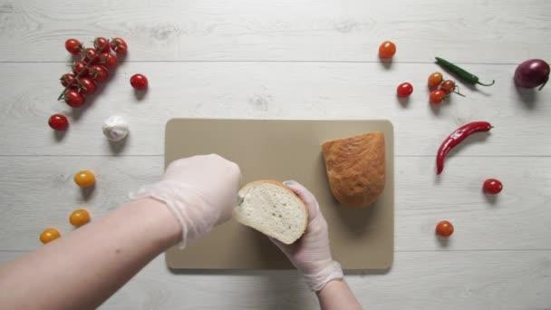 Top view of cutting fresh bread on plastic cutting board.