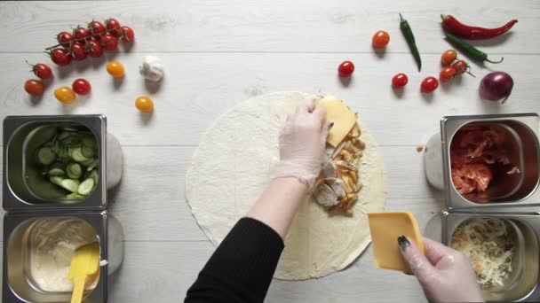 Chef hands in white gloves puts cheese on doner kebab shawarma in pita or lavash. Cooking shawarma with chicken, french fries, cheese and vegetable