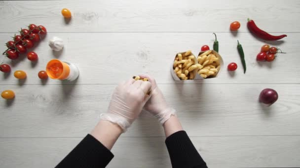 Chef in gloves move hot and delicious French Fries to paper bag