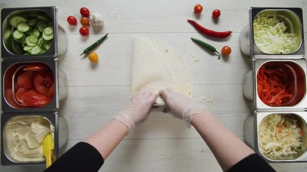 Top view of chef hands in white gloves wraps doner kebab shawarma in pita or lavash. Shawarma with chicken cutlet, pappers, cheese and vegetable