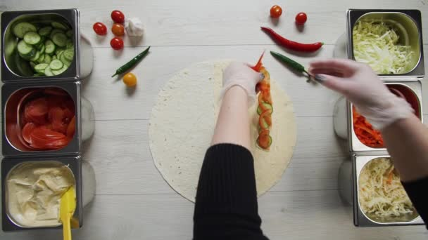 Top view of chef hands in white gloves puts peppres on doner kebab shawarma in pita or lavash. Shawarma with chicken cutlet, pappers, cheese and vegetable