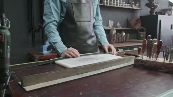 Der Gerber greift zu einem Werkzeug für die Arbeit mit Leder. Viele verschiedene Werkzeuge für die Handarbeit. Metallwerkzeuge