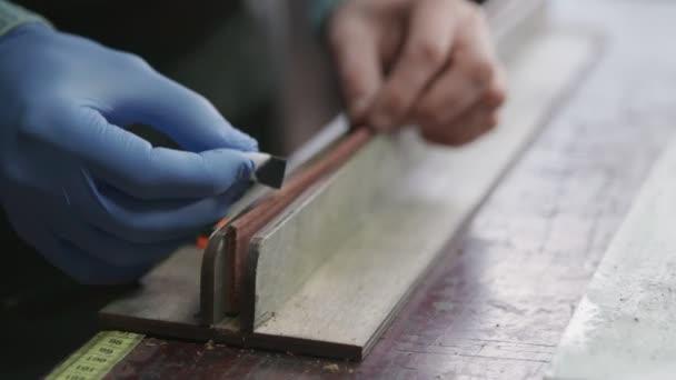Die Anwendung von Black Edge Dye auf Leder. Arbeitsprozess des Ledergürtels in der Lederwerkstatt.