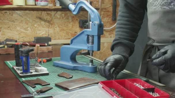 Nahaufnahme eines Mannes in schwarzen Handschuhen, der mit einer Presse Metallbeschläge montiert. Arbeitsprozess in der Lederwerkstatt.