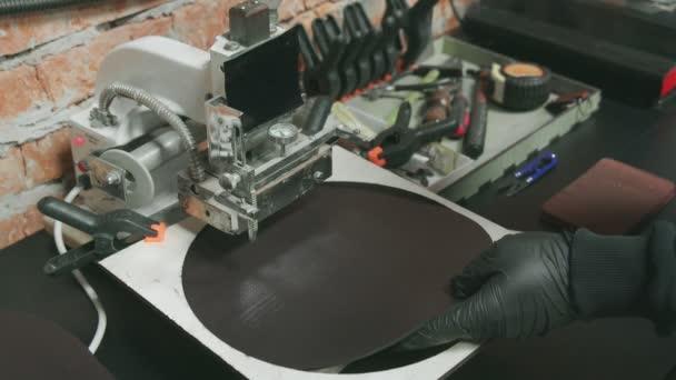 Großaufnahme eines Gerbers in schwarzen Handschuhen, der mit einer Presse Leder markiert. Arbeitsprozess in der Lederwerkstatt.