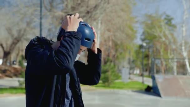 Mladý bmx jezdec v lékařské masce sedící na kole a v helmě