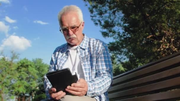 Alter Mann mit Brille und Schnurrbart sitzt auf Bank im Park und liest eBook