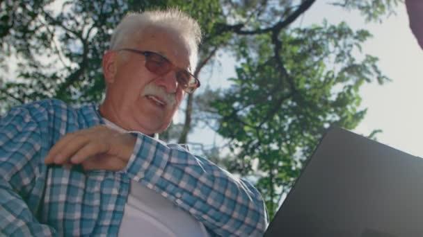 Alter Mann mit Brille beim Versuch, Computer im Park zu benutzen, aber er kippt. Er ruft jemanden an, der ihm helfen kann