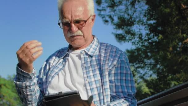 Ein älterer Mann mit Schnurrbart liest in einem Buch. Ein alter Mann ist heiß und wischt sich das Gesicht mit der Hand ab