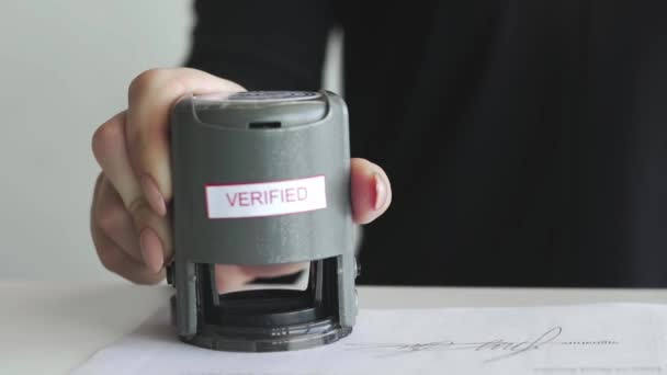 Female hand that puts an VERIFIED stamp in the contract or documents.